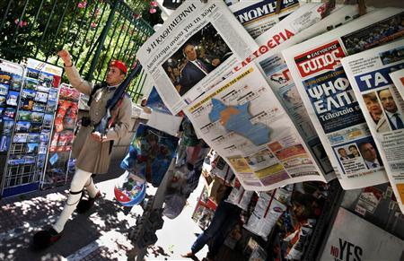 File picture of presidential guard marching by a newspaper stand featuring news about Greece's election results in Athens