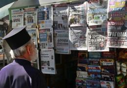 File picture of Greek Orthodox priest reading newspaper headlines at a kiosk in Athens