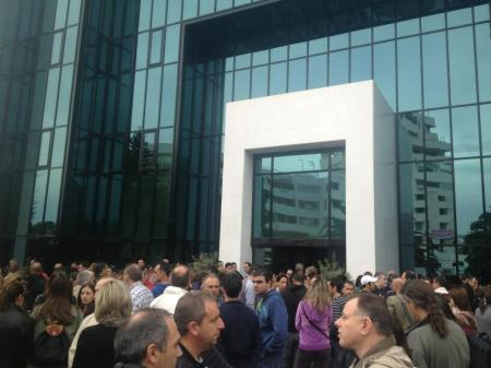 Εργαζόμενοι της Τράπεζας Κύπρου, συγκεντρωμένοι μπροστά από τα κεντρικά γραφεία της τράπεζας. Θέλουν να μάθουν τι συμβαίνει.