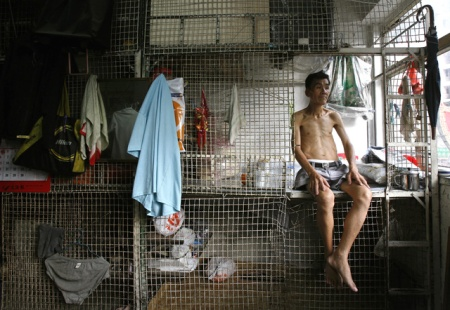 A man sits in his caged bed in Hong Kong September 16, 2009. Thousands of people live in similar caged homes, which cost an average monthly rental rate of $150, in one of the world's largest financial hubs, according to the Society for Community Organization, an NGO which helps those in need. REUTERS/Bobby Yip (CHINA BUSINESS SOCIETY IMAGES OF THE DAY)