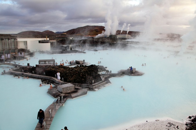Visitors pass along walkways spanning the Blue Lagoon geothermal spa as steam rises in Grindavik, Iceland, on Friday, Nov. 8, 2013. Iceland is on schedule to release a proposal on providing debt relief to households this month, Prime Minister Sigmundur D. Gunnlaugsson said. Photographer: Arnaldur Halldorsson/Bloomberg