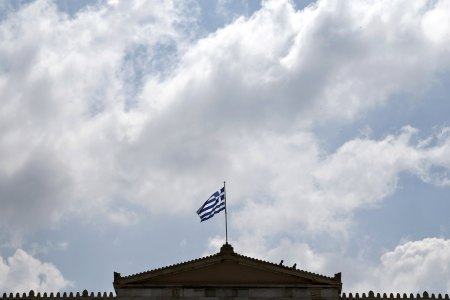 Employees of the Greek parliament walk on the roof of the building as a Greek national flag flutters atop in Athens June 9, 2015.  REUTERS/Alkis Konstantinidis