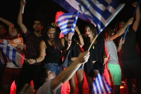 "ATHENS, GREECE - JULY 06:  People celebrate in front of the Greek parliament as the people of Greece reject the debt bailout by creditors on July 6, 2015 in Athens, Greece. The greek people have rejected a debt bailout in a referendum with nearly 62%  voting ""No"", against 38% voting ""Yes"" according to interior ministry figures  (Photo by Christopher Furlong/Getty Images)"