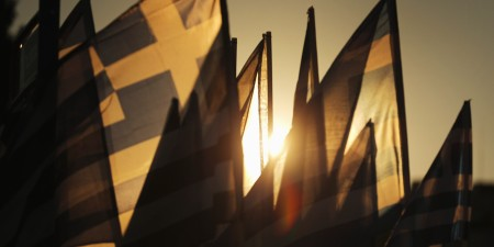 "ATHENS, GREECE - JULY 05: The sun sets through Grrek flags over the Greek parliament as the polls have now closed in the Greek austerity referendum and people are begining to gather in the squares of Athens waiting for the official result on July 5, 2015 in Athens, Greece. The people of Greece are going to the polls to decide if the country should accept the terms and conditions of a bailout with its creditors. Greek Prime Minister Alexis Tsipras is urging people to vote ""a proud no"" to European creditors' proposals, and ""live with dignity in Europe"". 'Yes' campaigners believe that a no vote would mean financial ruin for Greece and the loss of the Euro currency.  (Photo by Christopher Furlong/Getty Images)"