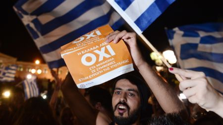 2015-07-05 22:06:44 People celebrate in Athens on July 5, 2015 after the first exit-polls of the Greek referendum. Over 60 percent of Greeks rejected further austerity dictated by the country's EU-IMF creditors in a referendum, results from 20 percent of polling stations showed. AFP PHOTO / LOUISA GOULIAMAKI